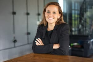 Closeup portrait of smiling young beautiful brown-haired woman looking at camera and standing with her arms crossed at reception desk in hotel. Beautiful business woman concept. Front view.