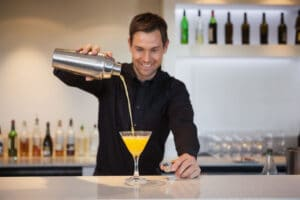 Smiling bartender pouring yellow cocktail into glass at the bar
