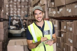 31351510 - warehouse worker smiling at camera with clipboard in a large warehouse