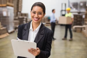 36390661 - smiling warehouse manager writing on clipboard in warehouse