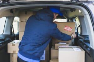 deliveryman-car-with-carton-boxes_23-2147767539