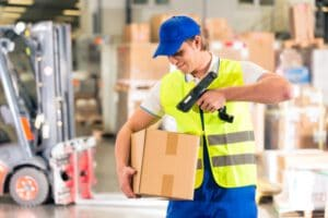 21401636 - warehouseman with protective vest and scanner, scans bar-code of package, he standing at warehouse of freight forwarding company