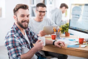 40227691 - getting the job done. handsome young man holding a cup of coffee and smiling while sitting at desk in the office with his colleagues working in the background